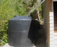 Rain water catchment tank farm. 'Dry' connecting pipe from gutter to tank. Filter basket inside tank access lid. San Juan Is. WA.